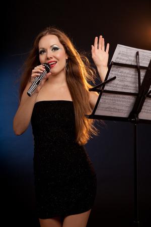 Portrait of a singing beautiful woman in black dress. Black background. Studio shot photo