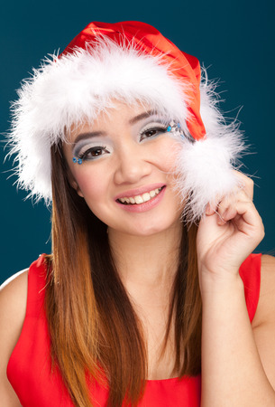 20 29: Beautiful christmas woman with santa costume. Studio shot. Blue background
