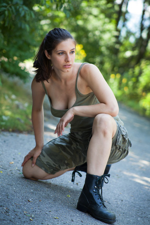 Beautiful militarry woman training in park photo