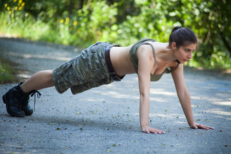 Beautiful military woman training push-ups in park photo