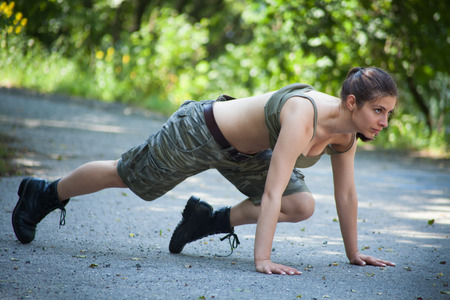 Beautiful sport woman training push-ups in park photo