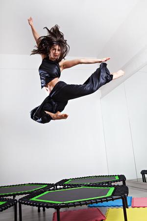 ninja: Jumping brunette woman on a trampoline. Studio shot.