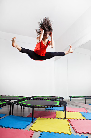 Jumping brunette woman on a trampoline. Studio shot. photo