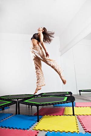 Jumping brunette woman on a trampoline. Studio shot.