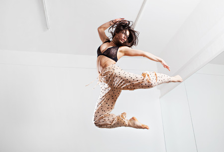 Jumping brunette woman on a trampoline. Studio shot.