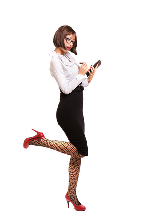 Sexy secretary with red high heels and glasses using tablet. Studio. White background. photo