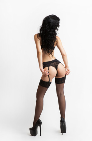 naked girl black hair: Sexy brunette woman with black lingerie and pantyhose in back. Studio. White background