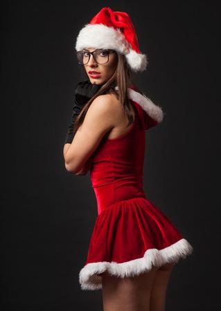 Beautiful young brunette woman dressed as Santa. Studio shot. Black background Stok Fotoğraf