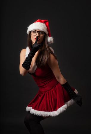 Beautiful young brunette woman dressed as Santa. Studio shot. Black background photo