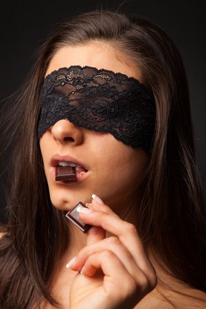 female sex: Beautiful woman with blindfold sexy eating chocolate on black background