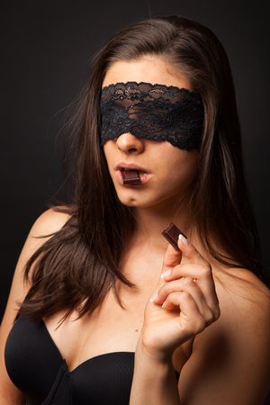 romantic sex: Beautiful woman with blindfold sexy eating chocolate on black background