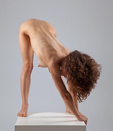 Sexy nude woman doing yoga exercises