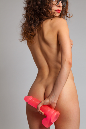 Sexy naked woman in back holding dildo