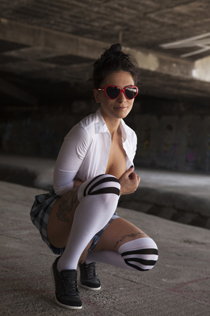 Sexy brunette with short skirts, shirt and sunglasses. Lolita stile. Graffiti wall background. Outdoors photos. Archivio Fotografico