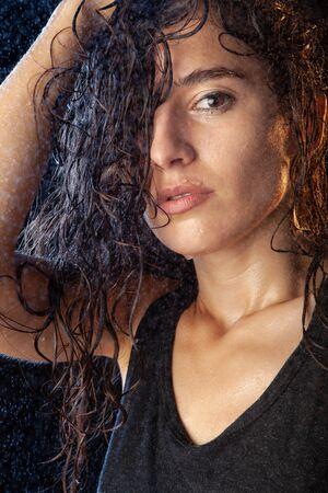 Closeup portrait of sexy wet brunette in black shirt, posing on black background. Splashing water on background. Stock Photo