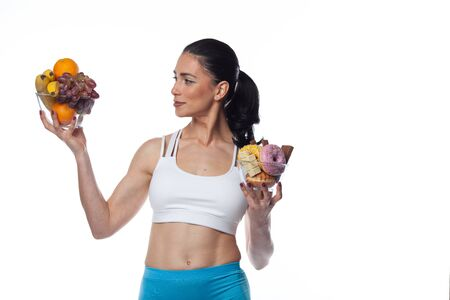 Sexy brunette woman in fitness suit eating fruits and candies. Studio shoot isolated on white background.