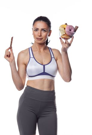 Sexy brunette woman in fitness suit eating candies. Studio shoot isolated on white background.
