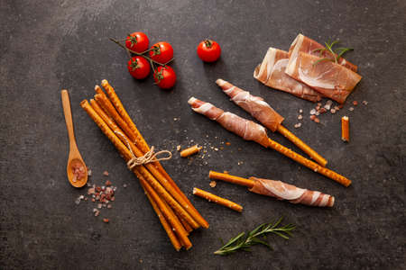 Dried prosciutto meat on the table served with bread sticks. Stok Fotoğraf