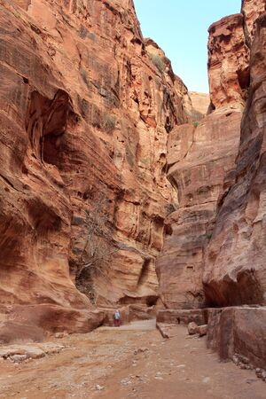 The Siq, the narrow slot-canyon that serves as the entrance passage to the hidden city of Petra, Jordan, seen here with tourists walking  photo