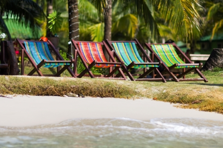 Colorful deckchairs on the beach of tropical island, Thailand photo