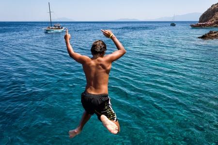 BODRUM, TURKEY - JULY 23  Unidentified boy jumping into sea from a yacht on July 23, 2011 in Bodrum, Turkey