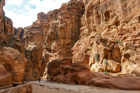 siq: The Siq, the narrow slot-canyon that serves as the entrance passage to the hidden city of Petra, Jordan, seen here with tourists walking. Stock Photo