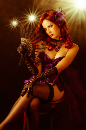 Beautiful young burlesque showgirl with fan sitting on stage. Stock Photo