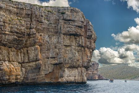 kornati national park: Boats passing impressively huge cliffs of Kornati National Park in Croatia