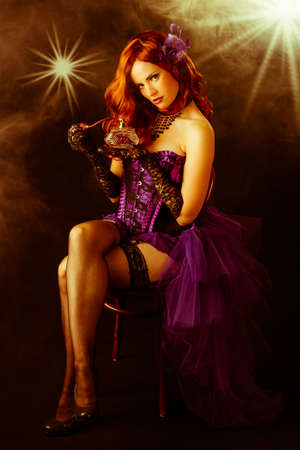 Beautiful young burlesque showgirl with perfume bottle on stage. photo