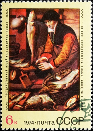 Postal stamp. Portrait of the woman displaying fish on a counter. photo