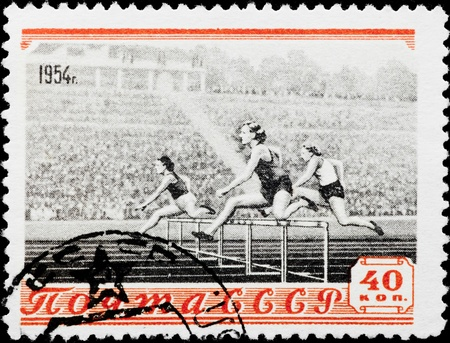 Postal stamp. Three sportswomen of a female jump through an obstruction Stock Photo