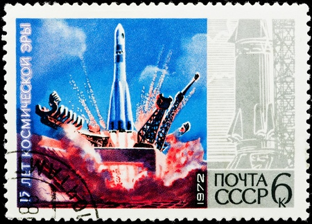 Postal stamp.  The space missile flies up from land in the blue sky. 17 years of a space age. photo