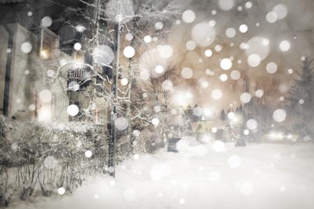 bilding: Winter night landscape, snowfall and street lights.