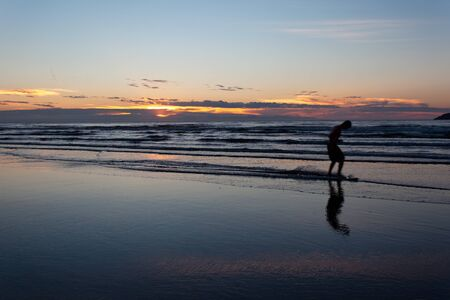 skim boarding at sunset Stock Photo