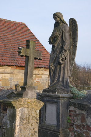 A detail of the old cemetery in a village in north Bohemia with statue of angel and cross, Czech Republic, from where the German population was displaced after WW II
