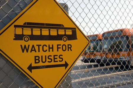 The Orange Line Buses behind a fence  The sign showing WATCH FOR BUSES