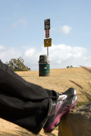 Waste container below a sign  Woman�s feet out of focus