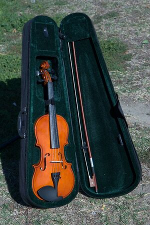 Orange violin inside a case set on the ground  Stock Photo
