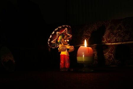 Doll with corkscrew, illuminated by a candle light at night