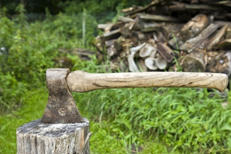 A woodsman's axe at rest in a block of wood