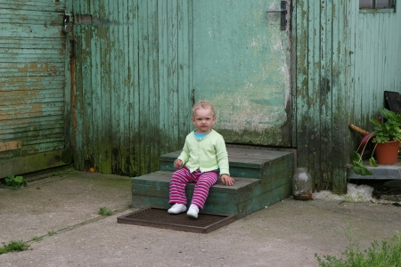 Little girl seating and looking ahead close to old house Stock Photo