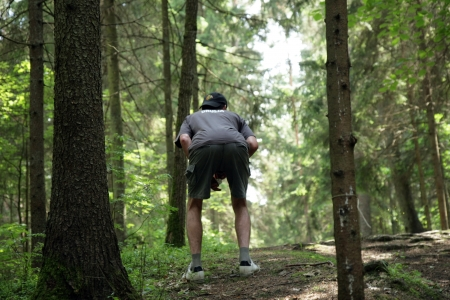 Man has stomachache in forest Stock Photo