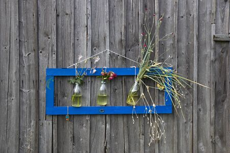Modern frame on the old wooden wall, with flowers inside of three bottles 写真素材