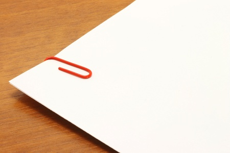 Piece of a white paper with a red clip over a wooden table photo
