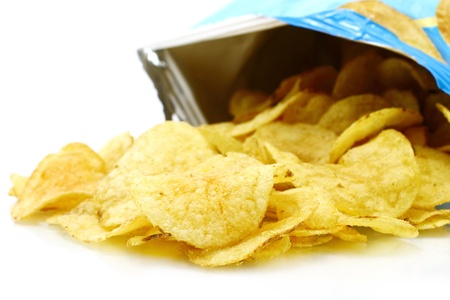 Potato chips poured out from packing on a white background  photo