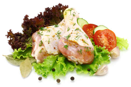 Raw chicken legs with vegetables on a white background photo