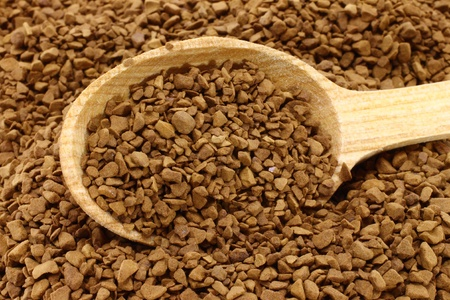 instant coffee: Ground coffee with wooden spoon on a coffee background