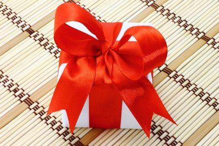 White box with red bow on a wooden background photo