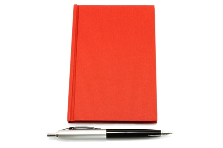 Red notepad with ball pen on a white background photo