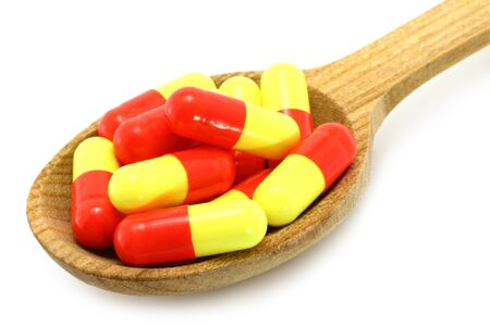 Wooden spoon with pills on a white background  photo